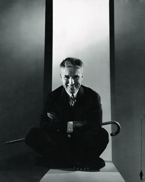 Charlie Chaplin Sitting on Floor Holding Cane